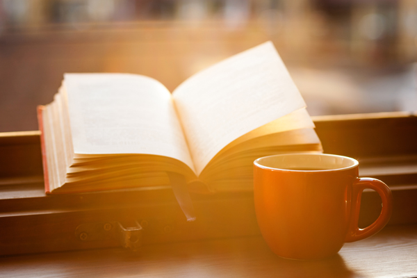 Books and a coffee cup on a windowsill